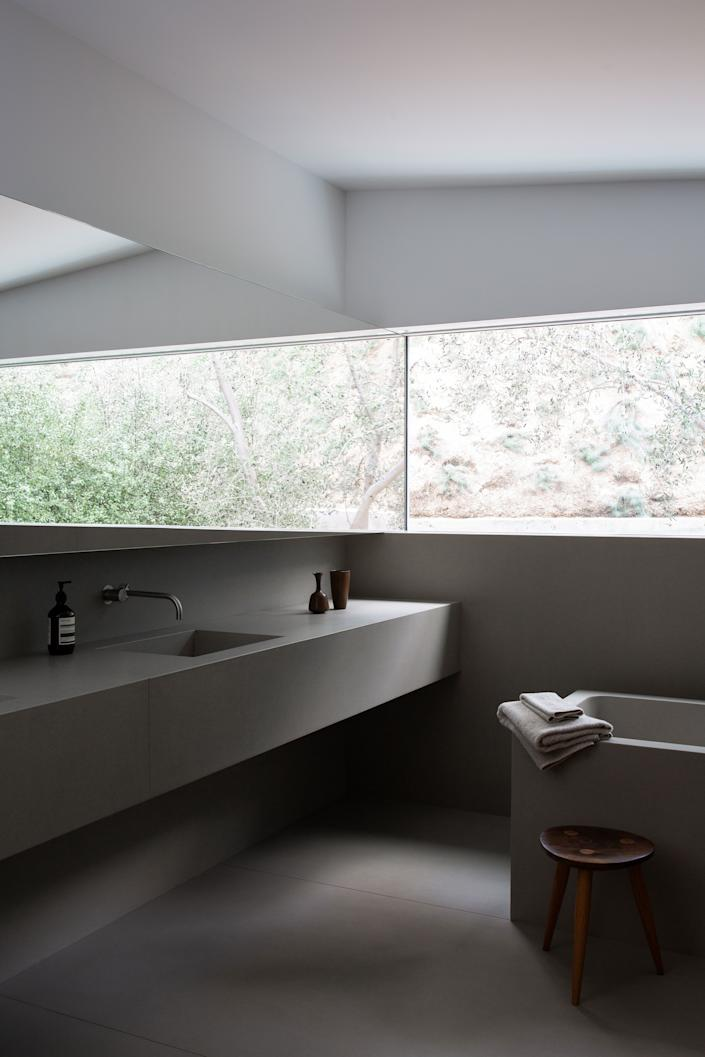 """<div class=""""caption""""> All of the bathrooms were inspired by those in architect John Pawson's Baron House. They feature concrete tubs and vanities, all in a muted gray concrete. The faucet is from d line and the towels are from Waterworks. </div>"""