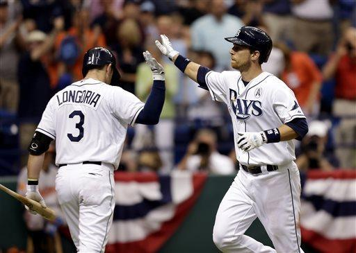 Tampa Bay Rays' Ben Zobrist, right, high fives teammate Evan Longoria after hitting a home run off Baltimore Orioles starting pitcher Jason Hammel during the fourth inning of an opening day baseball game Tuesday, April 2, 2013, in St. Petersburg, Fla. (AP Photo/Chris O'Meara)
