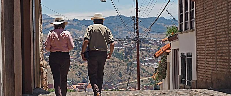 Man and woman, probably expats from Europe or North America, gingerly walk the streets of Sucre, Bolivia's capital.