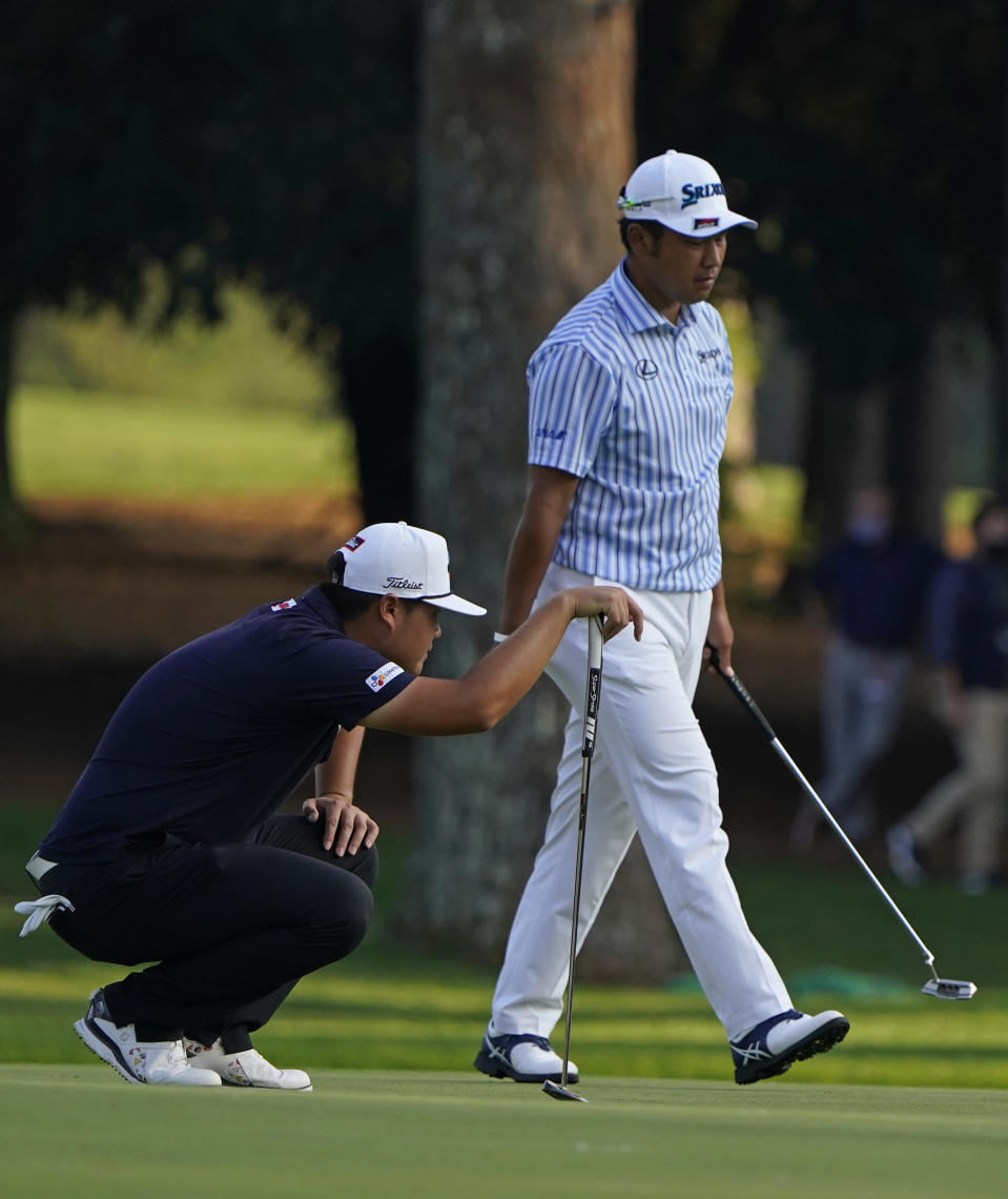 Sungjae Im, of South Korea, and Hideki Matsuyama, of Japan, wait to putt on the 15th green during the third round of the Masters golf tournament Saturday, Nov. 14, 2020, in Augusta, Ga. (AP Photo/Chris Carlson)