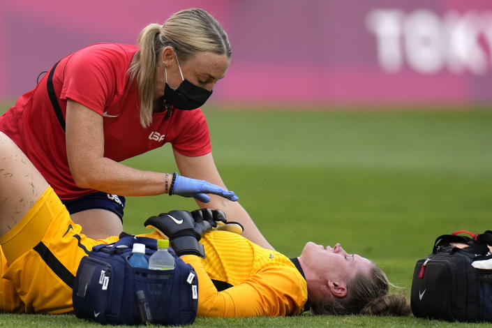 United States' goalkeeper Alyssa Naeher, below, lies on the field during a women's semifinal soccer match against Canada at the 2020 Summer Olympics, Monday, Aug. 2, 2021, in Kashima, Japan. (AP Photo/Fernando Vergara)