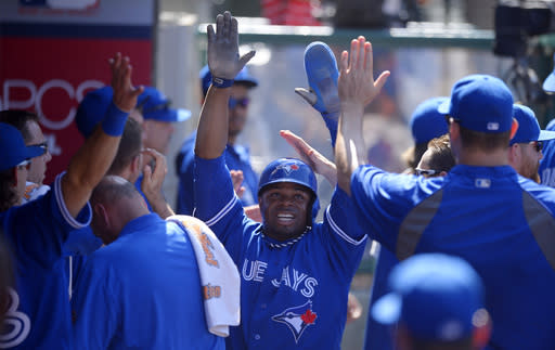 Toronto Blue Jays' Rajai Davis, center, is congratulated in the dugout after scoring on a single by Edwin Encarnacion during the ninth inning of their baseball game against the Los Angeles Angels, Sunday, Aug. 4, 2013, in Anaheim, Calif. (AP Photo/Mark J. Terrill)