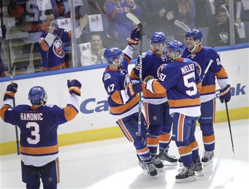 New York Islanders celebrate after Josh Bailey, third from right, scored an empty net goal during the third period of the NHL hockey game against the Pittsburgh Penguins, Thursday, March 29, 2012, in Uniondale, N.Y. The Islanders defeated the Penguins 5-3. (AP Photo/Seth Wenig)