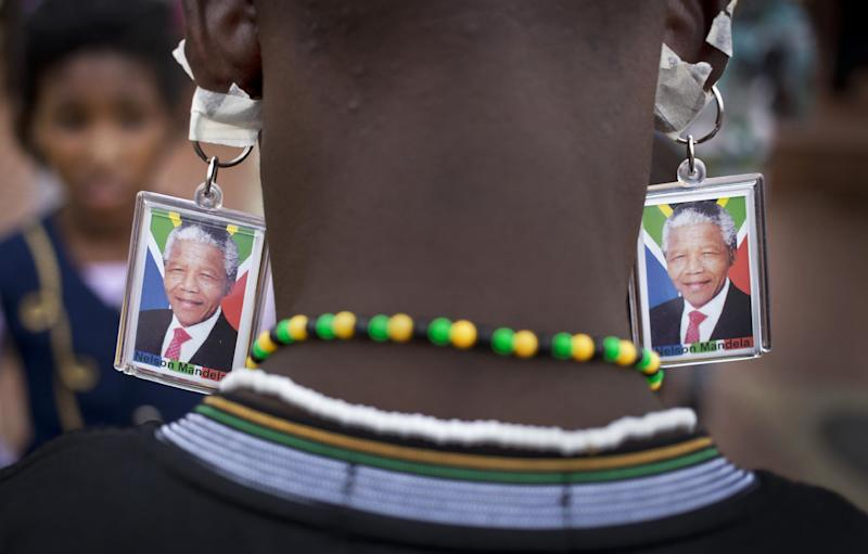 A man wears keyrings showing the face of Nelson Mandela taped to his ears to mimic earrings as he and others celebrate his life, in the street outside his old house in Soweto, Johannesburg, South Africa Friday, Dec. 6, 2013. Flags were lowered to half-staff and people in black townships, in upscale mostly white suburbs and in South Africa's vast rural grasslands commemorated Nelson Mandela with song, tears and prayers on Friday while pledging to adhere to the values of unity and democracy that he embodied. (AP Photo/Ben Curtis)