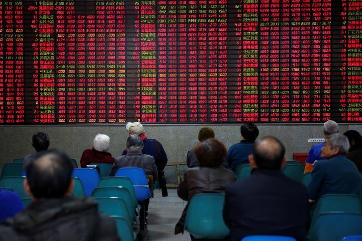 Investors look at an electronic board showing stock information on the first trading day after the New Year holiday at a brokerage house in Shanghai