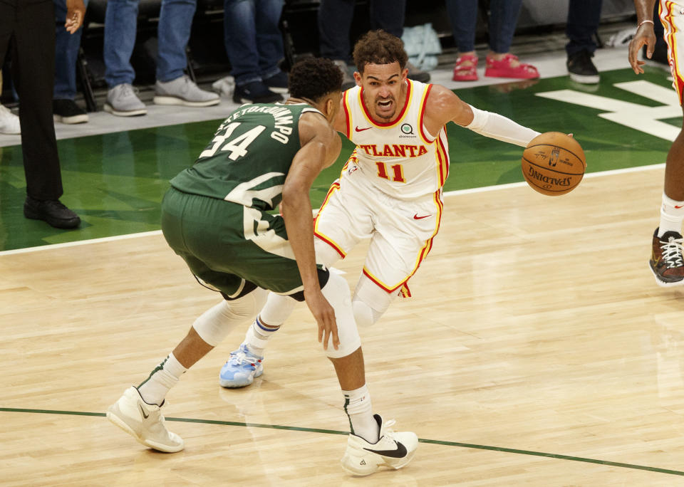 Trae Young drives for the basket against Giannis Antetokounmpo.