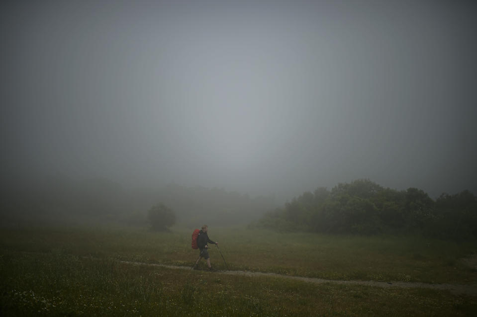 A pilgrim makes the St. James' Way walking at El Perdon mountain, near to Pamplona northern northern Spain, Tuesday, June 1, 2021. The pilgrims are trickling back to Spain's St. James Way after a year of being kept off the trail due to the pandemic. Many have committed to putting their lives on hold for days or weeks to walk to the medieval cathedral in Santiago de Compostela in hopes of healing wounds caused by the coronavirus. (AP Photo/Alvaro Barrientos)