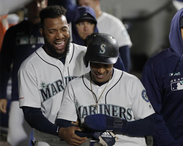 Seattle Mariners' Domingo Santana, left, and Mallex Smith, right, smile in the dugout after Smith scored on a bases-loaded walk drawn by Kyle Seager during the seventh inning of the team's baseball game against the Baltimore Orioles, Thursday, June 20, 2019, in Seattle. (AP Photo/Ted S. Warren)