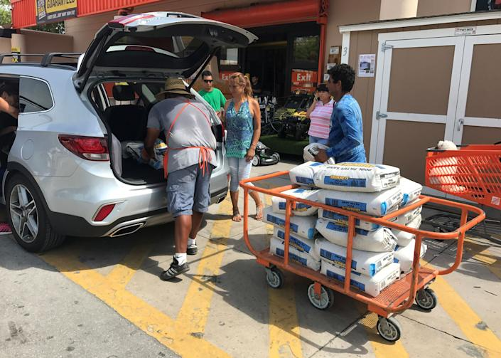 A Home Depot store employee helps to load bags of sand for customers in the Little Havana neighborhood in Miami.