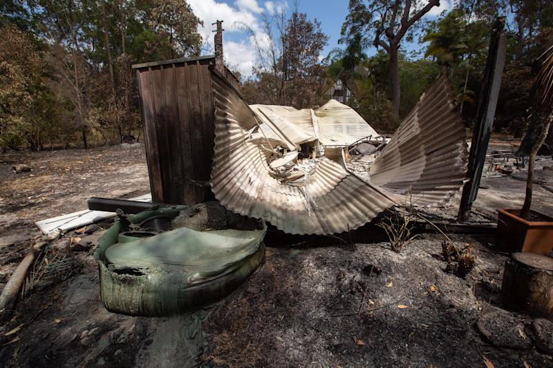 A burnt-out car, cabin and sheds owned by resident Thorsten Kels at Lake Cooroibah Road, Noosa on Monday. Source: AAP/Rob Maccoll