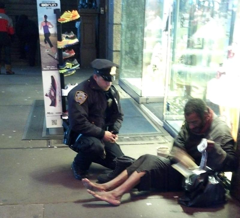"This photo provided by Jennifer Foster shows New York City Police Officer Larry DePrimo presenting a barefoot homeless man in New York's Time Square with boots Nov. 14, 2012 . Foster was visiting New York with her boyfriend on Nov. 14, when she came across the shoeless man asking for change in Times Square. As she was about to approach him, she said the officer  came up to the man with a pair of all-weather boots and thermal socks on the frigid night. She took the picture on her cellphone. It was posted Tuesday night to the NYPD's official Facebook page and became an instant hit. More than 350,000 users ""liked"" it as of Thursday afternoon, and over 100,000 shared it. (AP Photo/Jennifer Foster)"