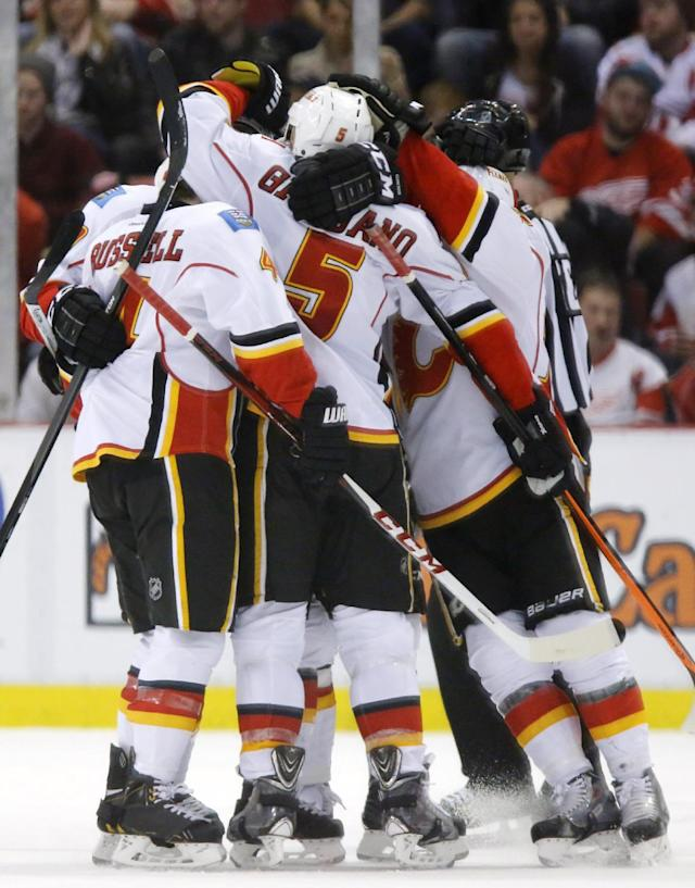 Calgary Flames' Mark Giordano (5) celebrates his goal against the Detroit Red Wings with teammates during the second period of an NHL hockey game, Thursday, Dec. 19, 2013, in Detroit. (AP Photo/Duane Burleson)