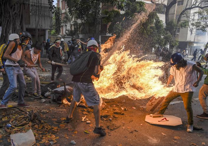 <p>Demonstrator catches fire: Víctor Salazar catches fire after a motorcycle explodes, during a street protest is Caracas, Venezuela, May 3, 2017.<br>José Víctor Salazar Balza (28) caught fire after the gas tank on a motorcycle exploded, during a protest against the Venezuelan president, Nicolás Maduro, in Caracas. Violent clashes had broken out between demonstrators and the national guard. The motorcycle, belonging to a member of the national guard, was apparently being destroyed by protesters.<br>Accounts of the incident differ, but some say that an object thrown by protesters caused the gas tank to explode. Further reports maintain that Salazar's clothing caught fire so readily because he was doused in petrol either by a bomb he was carrying, or that of a fellow protestor.<br>Salazar suffered severe burns to more than 70% of his body, but survived the incident. (Photo: Juan Barreto/AFP) </p>