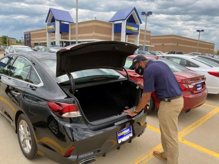 Brandon Parrum, general manager of CarMax's Des Moines store, shows off one of the many vehicles that customers can arrange to buy online and collect at the store