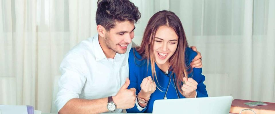 Woman sitting working at laptop in the office celebrating success pumping fists and man hugs and supports her showing thumbs up like hand gesture.