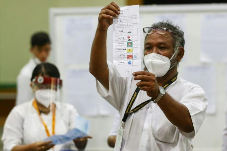 An election official holds up a ballot as votes are counted at a polling station in Myanmar on November 8, 2020