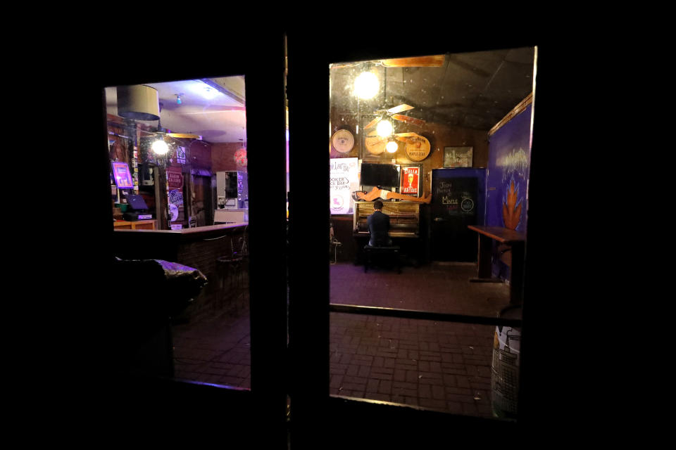 In this April 29, 2020, photo, pianist Josh Paxton performs a livestream concert from inside the closed and empty Maple Leaf Bar in New Orleans. Music clubs all over the nation — pop culture icons like the Troubadour in West Hollywood, the Bluebird Cafe in Nashville, The Bitter End in New York's Greenwich Village — are shuttered. And owners fear for the future of their businesses and of a musical way of life. (AP Photo/Gerald Herbert)