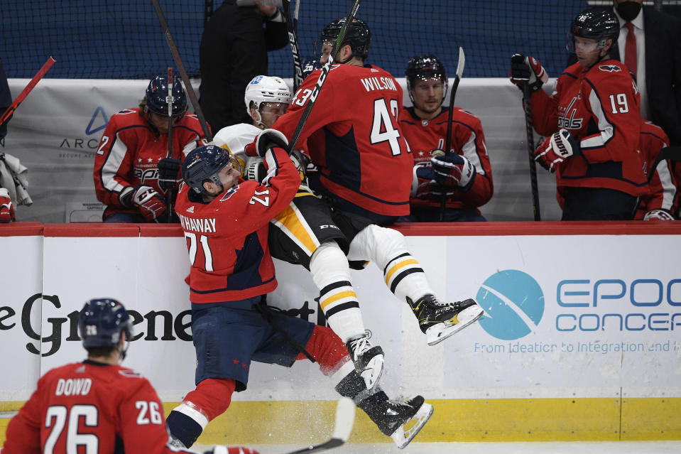 Washington Capitals right wing Garnet Hathaway (21) checks Pittsburgh Penguins defenseman Mike Matheson, center, during the third period of an NHL hockey game, Thursday, Feb. 25, 2021, in Washington. Capitals right wing Tom Wilson (43) looks on. (AP Photo/Nick Wass)