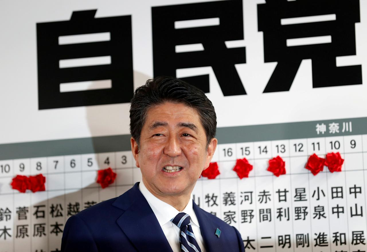 Japan's Prime Minister Shinzo Abe, leader of the Liberal Democratic Party (LDP), smiles as he puts a rosette on the name of a candidate who is expected to win the lower house election, at the LDP headquarters in Tokyo, Japan, October 22, 2017. EUTERS/Kim Kyung-Hoon     TPX IMAGES OF THE DAY