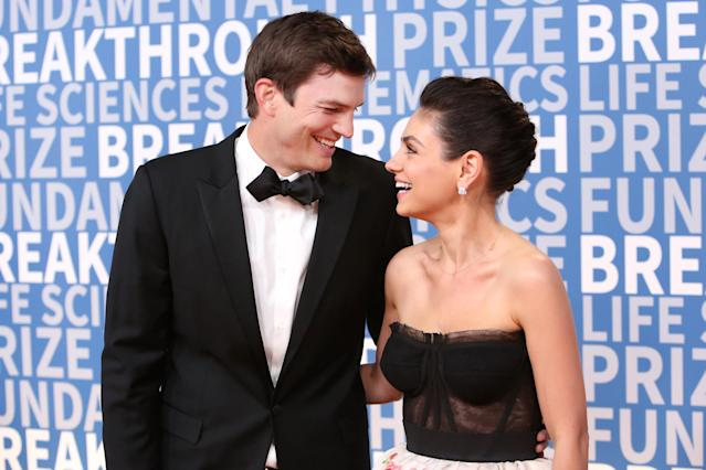 Ashton Kutcher and Mila Kunis look in love on the red carpet. (Photo: Getty Images)