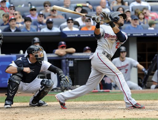 Minnesota Twins' Pedro Florimon follows through on a two-run home run as New York Yankees catcher Austin Romine, left, looks on during the eighth inning of a baseball game Saturday, July 13, 2013, at Yankee Stadium in New York. (AP Photo/Bill Kostroun)