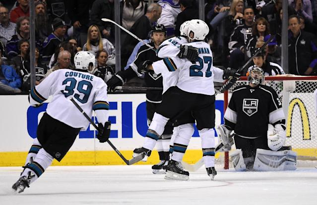 San Jose Sharks center Patrick Marleau, center, celebrates his game-winning goal with defenseman Scott Hannan, second from right, as Los Angeles Kings goalie Jonathan Quick, right, looks on and center Logan Couture skates in during the overtime period in Game 3 of an NHL hockey first-round playoff series, Tuesday, April 22, 2014, in Los Angeles. The Sharks won 4-3. (AP Photo/Mark J. Terrill)