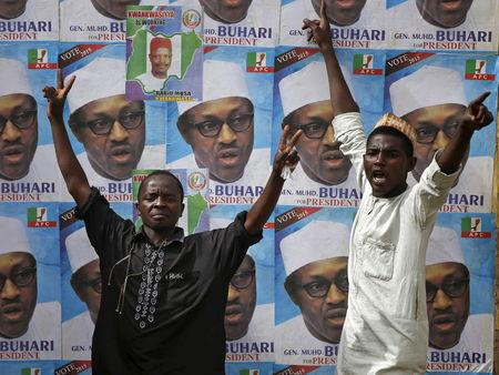 Supporters of presidential candidate Buhari gesture in front of his election posters in Kano