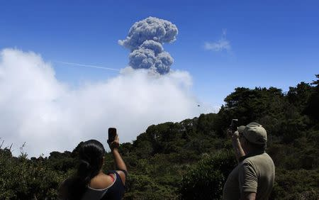 People take pictures of an eruption of the Turrialba volcano, from San Gerardo de Irazu near Turrialba, March 13, 2015. REUTERS/Juan Carlos Ulate