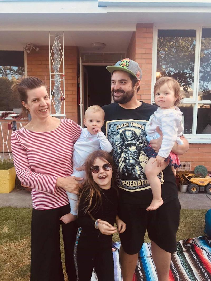 Virginia Carpenter and Adrien are holding their twin daughters and standing with Ms Carpenter's eight-year-old daughter.