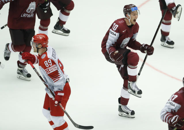 Denmark's Mikkel Boedker, left, skates past Latvia's Rihards Bukarts, right, who celebrates after the Ice Hockey World Championships group B match between Denmark and Latvia at the Jyske Bank Boxen arena in Herning, Denmark, Tuesday, May 15, 2018. (AP Photo/Petr David Josek)