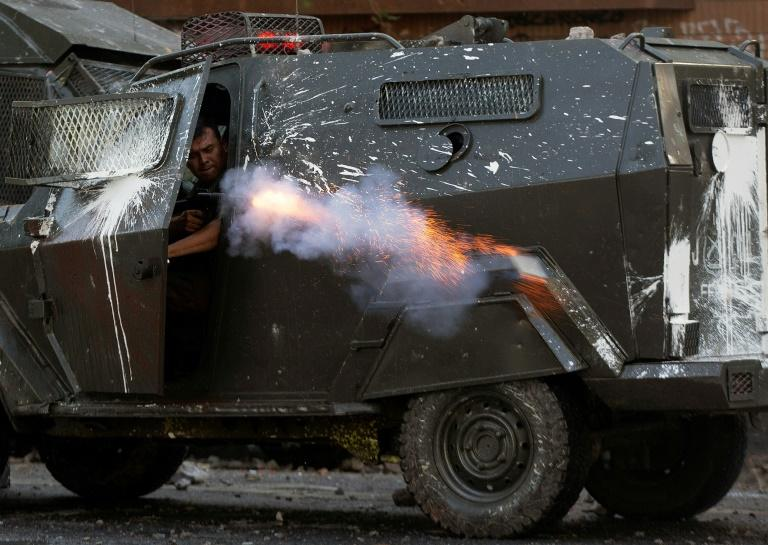 A riot policeman shoots at demonstrators during a protest against the government in Santiago on Friday