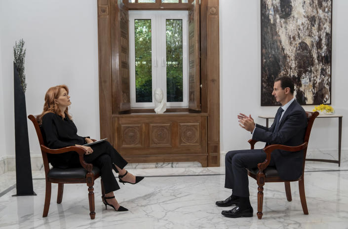 "In this photo released on Monday Nov. 9, 2019 by the Syrian official news agency SANA, Syrian President Bashar Assad, right, speaks during an interview with Monica Maggioni, left, the CEO of Italy's Rai News 24, in Damascus, Syria. Assad said in an interview aired Monday that the global chemical weapons watchdog has faked and falsified a report over an attack near the capital Damascus last year ""just because the Americans wanted them to do so."" (SANA via AP)"