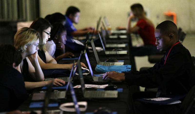 Job seekers work on their resumes during the Opportunity Fair and Forum employment event in Dallas. (AP Photo/LM Otero)