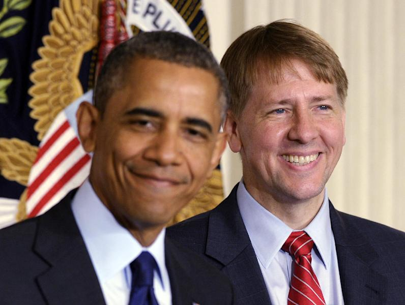 President Barack Obama, left, smiles as he stands with Richard Cordray, right, the new director of the Consumer Financial Protection Bureau, during a statement in the State Dining Room of the White House in Washington, Wednesday, July 17, 2013. The Senate voted on Tuesday, July 16, 2013, to end a two-year Republican blockade that was preventing Cordray from winning confirmation as director of the Consumer Financial Protection Bureau. (AP Photo/Susan Walsh)