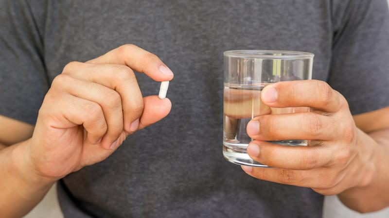 Man holding a pill and a glass of water.