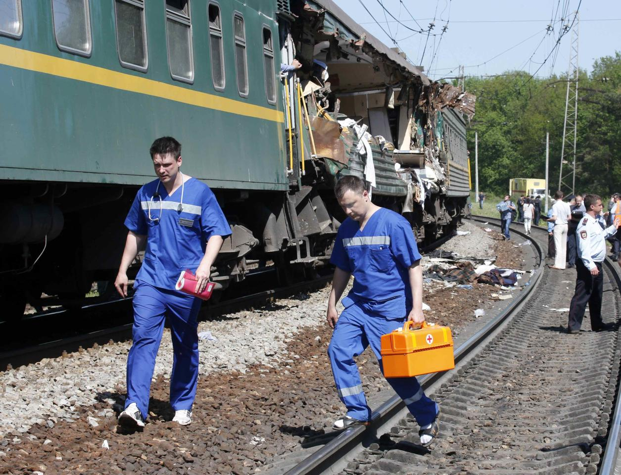Medical personnel walk near a passenger train damaged in a collision with a freight train in Moscow region May 20, 2014. A passenger train on its way to Moldova collided with a freight train near Moscow on Tuesday, killing at least four people and injuring 15, a spokeswoman for Russia's Emergencies Ministry said. The reason for the collision, near the town of Naro-Fominsk 55 km (34 miles) southwest of Moscow, was not immediately clear. REUTERS/Grigory Dukor (RUSSIA - Tags: DISASTER TRANSPORT)