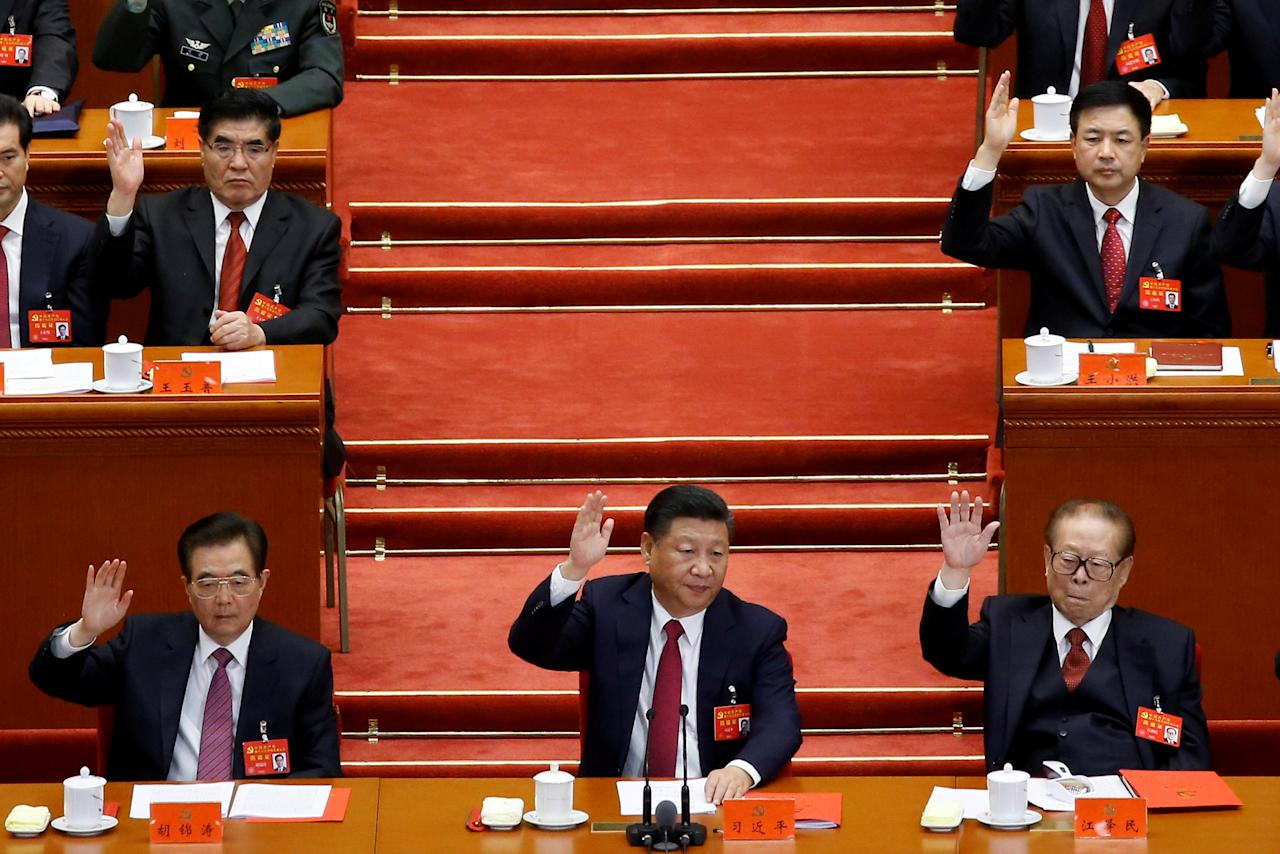 (L to R) Former Chinese president Hu Jintao, Chinese President Xi Jinping and former Chinese president Jiang Zemin raise their hands as they take a vote at the closing session of the 19th National Congress of the Communist Party of China, in Beijing, China October 24, 2017.  REUTERS/Thomas Peter     TPX IMAGES OF THE DAY
