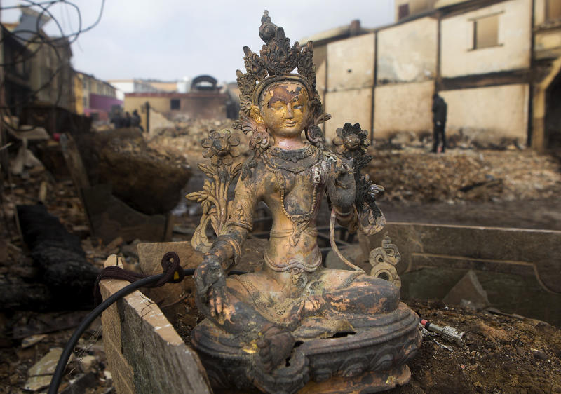 In this Sunday, Jan. 12, 2014 photo, a burned Buddha sculpture sits on the debris of burnt houses in the ancient town of Dukezong after a fire broke out on last Saturday, in Shangri-la county in southwest China's Yunnan province. A fire prevention system costing more than $1 million wasn't functioning and failed to prevent a blaze that razed the ancient tourist town, the fire service said Monday. (AP Photo) CHINA OUT