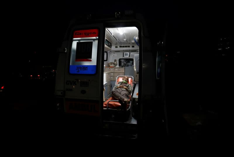 A patient lies inside an ambulance waiting in a queue to enter a COVID-19 hospital in Ahmedabad