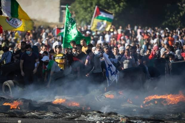 Palestinians clash with Israeli forces at the Hawara checkpoint.