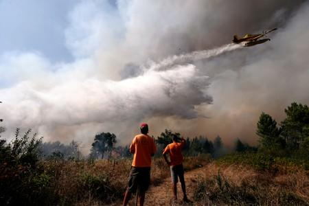 A firefighting plane dumps water on a forest fire next to the village of Vila de Rei