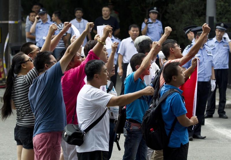 A group of Chinese protesters chant slogans in front of the Japanese Embassy during a protest against the arrests of 14 activists, in Beijing Thursday, Aug. 16, 2012. The 14 people who included Hong Kong residents and mainland Chinese, had traveled by boat from Hong Kong to a set of uninhabited islands controlled by Japan but also claimed by China and Taiwan, and were arrested on Wednesday. (AP Photo/Andy Wong)