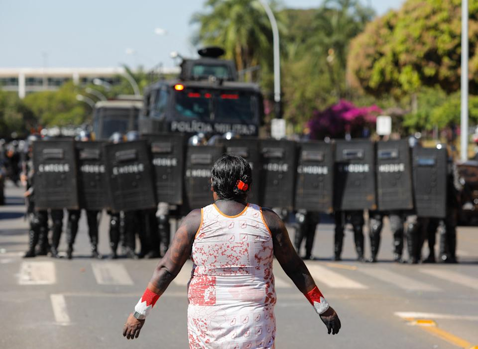An indigenous woman is seen near a line of riot police during a protest outside the National Congress in Brasilia, on June 22, 2021. - Indigenous people are camping in the capital to oppose a bill said to limit recognition of reserve lands. (Photo by Sergio Lima / AFP) (Photo by SERGIO LIMA/AFP via Getty Images)