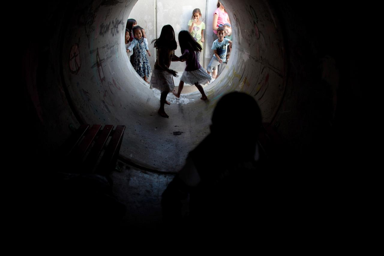 KIRYAT MALACHI, ISRAEL - NOVEMBER 15: (ISRAEL OUT)  Israeli children play in a large concrete pipe used as a bomb shelter between rocket attacks from the Gaza Strip on November 15, 2012 in Kiryat Malachi, Israel. The rocket attack happened some 24 hours after the IDF targeted nearly 200 sites in the Gaza Strip, killing Ahmed Jabari, a top military commander of Hamas, in the process. (Photo by Uriel Sinai/Getty Images)