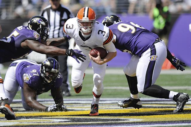 Cleveland Browns quarterback Brandon Weeden (3) scrambles between Baltimore Ravens outside linebacker Terrell Suggs, top left, defensive end Arthur Jones (97) and defensive end Marcus Spears, right, during the first half of an NFL football game in Baltimore, Md., Sunday, Sept. 15, 2013. (AP Photo/Nick Wass)