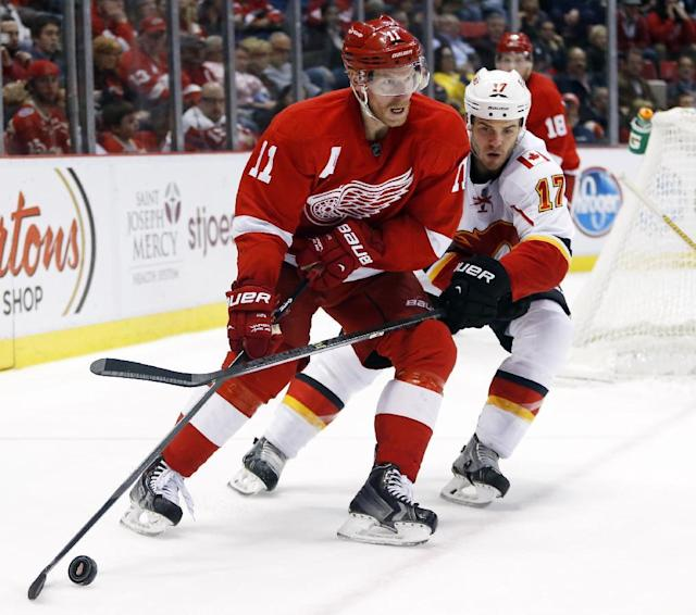Detroit Red Wings' Daniel Alfredsson (11) keeps to puck out of reach of Calgary Flames' Lance Bouma (17) during the second period of an NHL hockey game, Thursday, Dec. 19, 2013, in Detroit. Alfredson scored two goals and had one assist in the Red Wings 3-2 overtime win. (AP Photo/Duane Burleson)