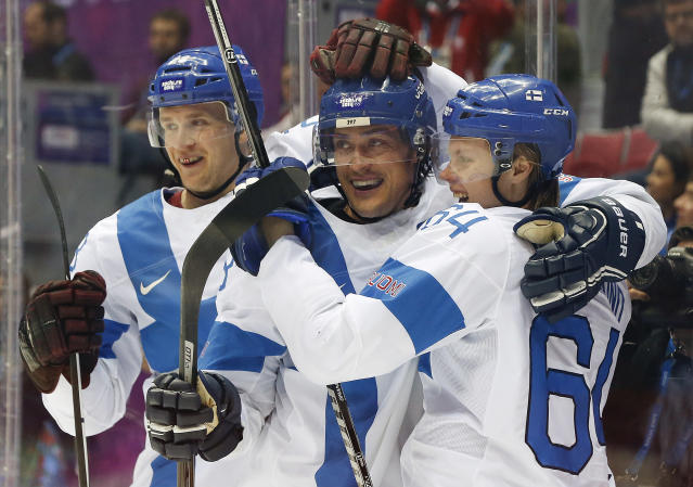 Finland forward Teemu Selanne, center, celebrates with teammates forward Lauri Korpikoski, left, and forward Mikael Grandlund after scoring a goal against the USA during the second period of the men's bronze medal ice hockey game at the 2014 Winter Olympics, Saturday, Feb. 22, 2014, in Sochi, Russia. (AP Photo/Mark Humphrey)