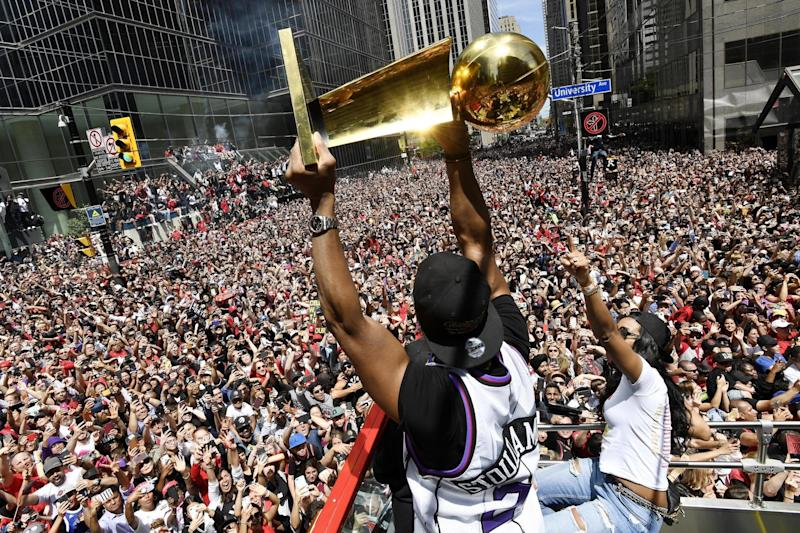 Toronto Raptors guard Kyle Lowry holds the Larry O'Brien Championship Trophy up for fans during the victory parade (AP)