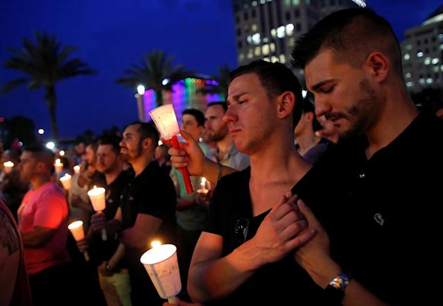 <p>People gather for a candlelight vigil during a memorial service for the victims of the shooting at the Pulse gay nightclub in Orlando on June 13, 2016. (Photo: Jim Young/Reuters) </p>