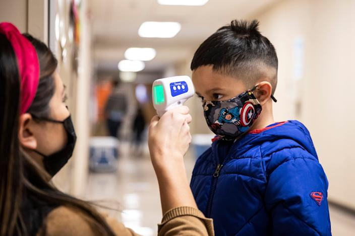A preschool student gets his temperature checked as he walks into Dawes Elementary School in Chicago on Jan. 11, 2021.